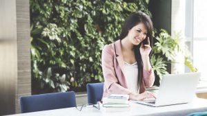 Frau telefoniert und arbeitet am Laptop